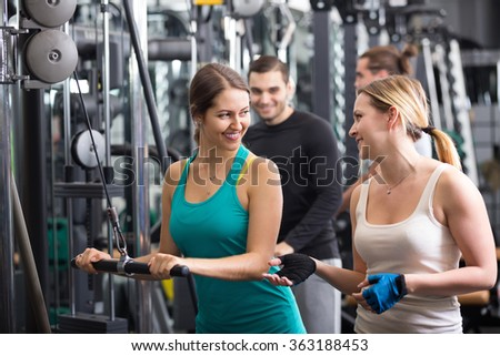 Positive young adults doing powerlifting on machines in fitness club
