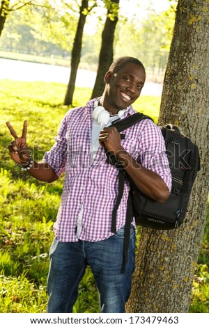 Positive young african american with backpack and earphones in a park - stock photo
