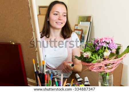 Positive young artist in the process of creating a new picture - stock photo