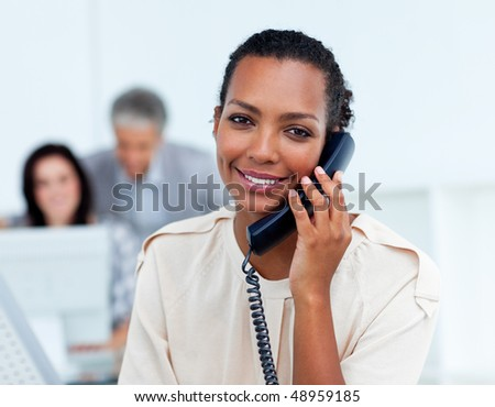 Positive young businesswoman talking on phone at work - stock photo