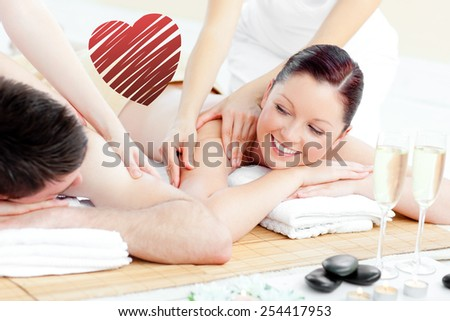 Positive young couple enjoying a back massage against red heart - stock photo