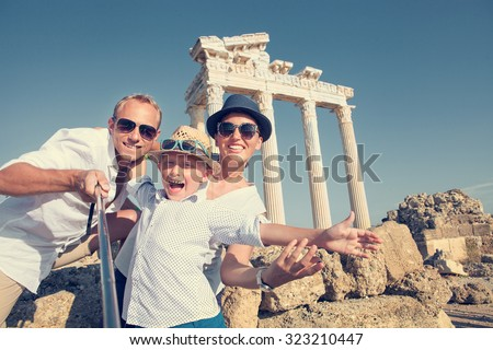 Positive young family take a selfie photo near antique colonnade - stock photo