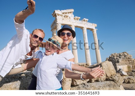 Positive young family take a summer vacation selfie photo on antique sights view - stock photo
