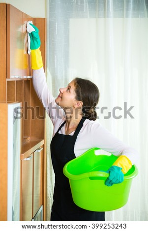 Positive young housewife in apron and rubber gloves dusting furniture at home - stock photo