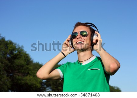 Positive young man wearing sunglasses and headphones - stock photo