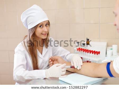 Positive young nurse taking blood sample  from patient in clinic - stock photo