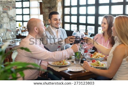 Positive young people enjoying the food and smiling at tavern  - stock photo