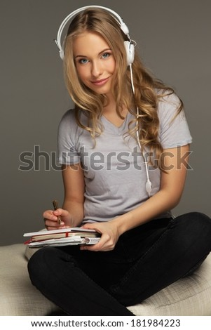 Positive young woman student with notebook listens to music - stock photo