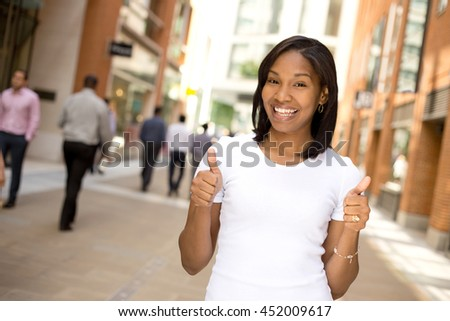 positive young woman with her thumbs up - stock photo