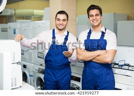 Positive young workers in uniform working at household appliances store - stock photo