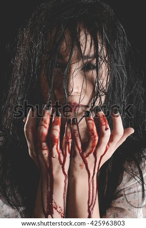 Possessed Woman with bloody hands - stock photo