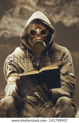 Post apocalyptic survivor in gas mask reading a book - stock photo