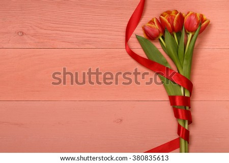 Post blog social media 8 march. View from above with copy space. Banner template layout mockup for woman day. Red wooden table, top view on workplace. Pink tulips over shabby white wooden table. - stock photo