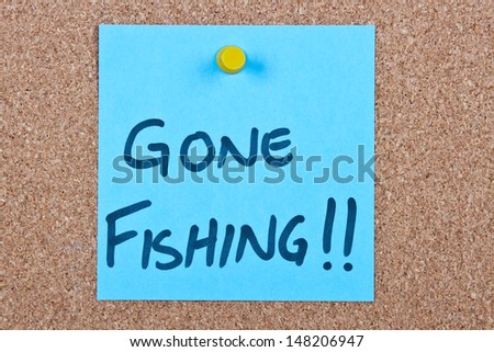 Post it note on wood in blue with gone fishing - stock photo