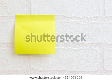Post it note or sticky note on white wallpaper brick pattern use for background - stock photo
