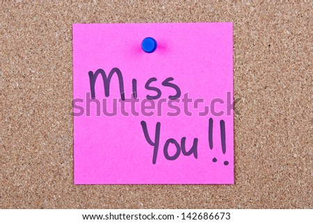 Post it note pink with miss you message on cork - stock photo