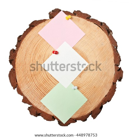 Post-it notes pinned on a wooden slice - stock photo