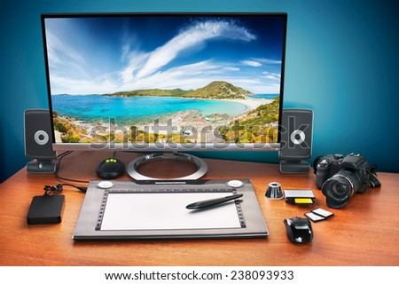 Post production desk with digital camera, memory cards, graphic tablet, and monitor to advertise youself and your work. Monitor with seascape  photo. - stock photo