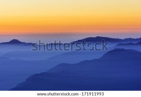 post sunset scene in Mountain valley filled with fog - stock photo