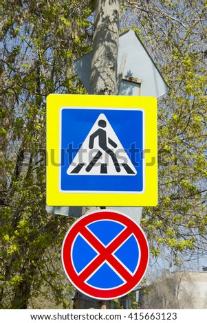 Post with road signs and pedestrian Parking is prohibited on the background of green trees - stock photo