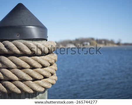 Post with rope at the side of a pier for docking and securing boats.  Selective focus on the rope.  Background of shoreline and water are obvious but deliberately blurred.   - stock photo