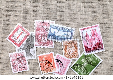 Postage stamps on burlap background - stock photo