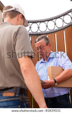 Postal service - delivery of a package; the postman is giving the package to the customer in front of his house - stock photo