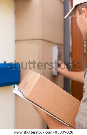 Postal service - delivery of a package; the postman is standing in front of the door and rings the bell - stock photo