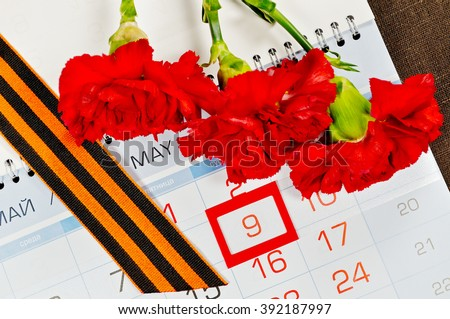 Postcard for Victory Day in Great Patriotic War in Russia- St George ribbon and red carnations over the calendar with framed 9th May date. 9 May concept.   - stock photo