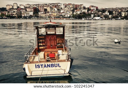Postcard from Istanbul. Motor boat by the Golden Horn - Istanbul, Turkey. The Beyoglu district in the background. - stock photo
