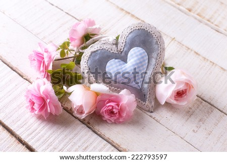 Postcard with fresh roses and decorative heart on wooden background. Selective focus. - stock photo