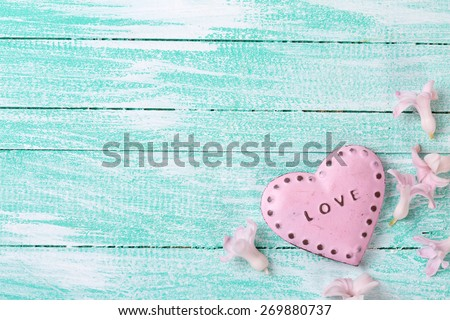Postcard with little flowers hyacinths  and decorative heart on turquoise painted wooden planks. Selective focus. Place for text.  - stock photo