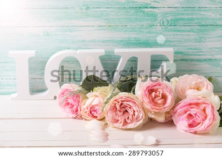 Postcard with sweet pink roses flowers and word love  in ray of light on white painted wooden background against turquoise wall. Selective focus. Place for text. - stock photo