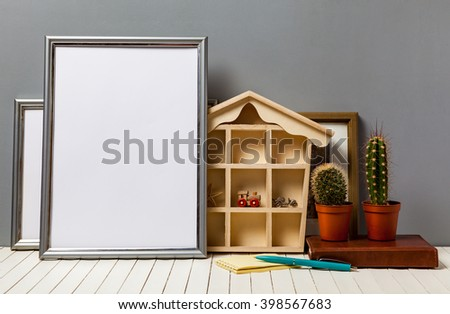 poster frame with office items and cactus on wooden table - stock photo