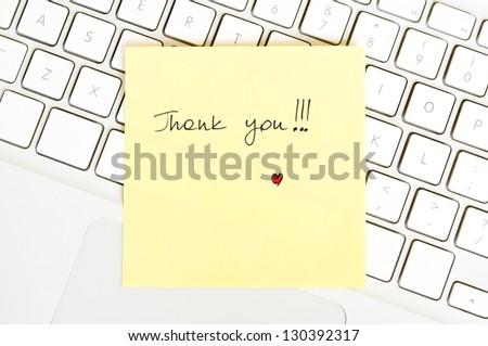 Postit note saying Thank You arranged on a laptop keyboard - stock photo
