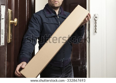 Postman brings a parcel in special size - stock photo