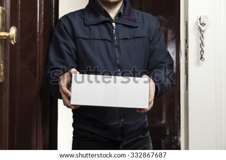 Postman brings a white package - stock photo