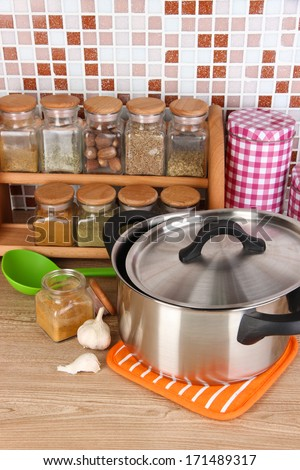 Pot and spices in kitchen on table on mosaic tiles background - stock photo