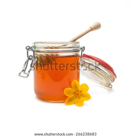 pot of golden nature honey with wooden drizzler on white - stock photo