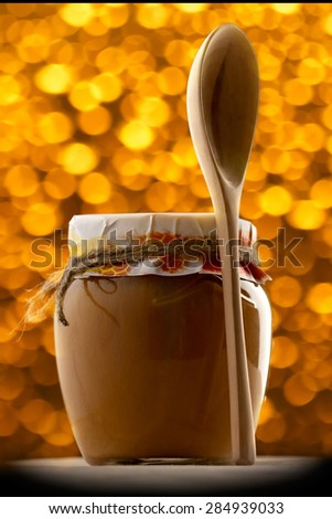 Pot of honey and a wooden spoon on blur - stock photo
