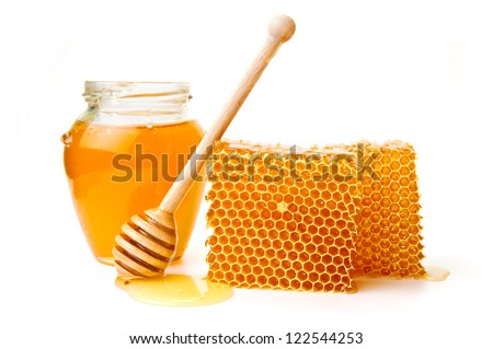 Pot of honey and wooden stick are on a table - stock photo