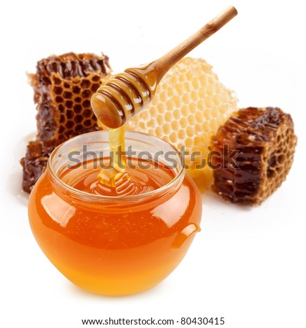 Pot of honey and wooden stick are on a table. - stock photo