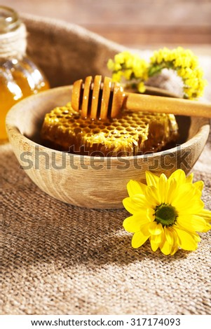 Pot of honey, honeycomb and dipper in bowl on sackcloth - stock photo