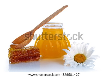 Pot of honey, wooden spoon and honeycomb isolated on white - stock photo