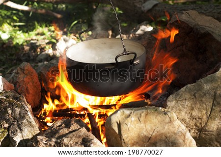 Pot water on the fire, tourists kettle on hot campfire. Camping photo. - stock photo