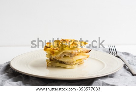Potato casserole with meat on the wooden table - stock photo
