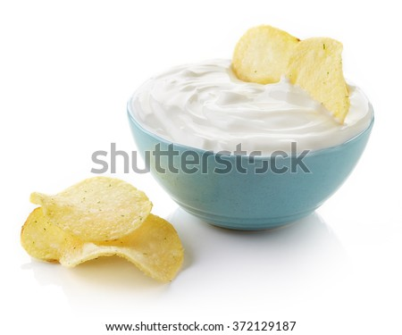 Potato chips and bowl of dip on white background - stock photo