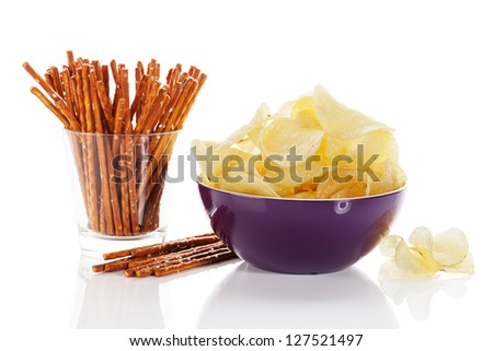 potato chips in a bowl with pretzel sticks in a glass on white background - stock photo