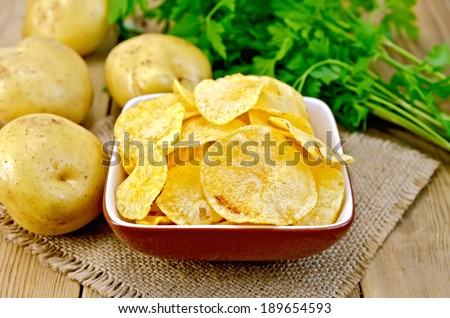 Potato chips in a clay bowl on a napkin from a burlap, fresh potatoes, parsley on a wooden boards backgroun - stock photo