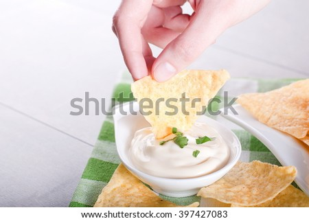 Potato chips in a hand dipped in sauce - stock photo